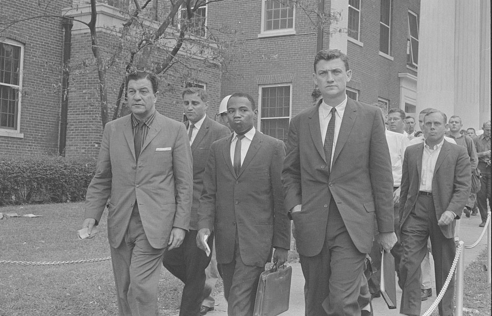 James Meredith walking on the campus of the University of Mississippi, accompanied by U.S. marshals.